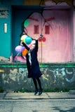 Giovane donna felice che salta su mentre tenere balloons Immagine Stock