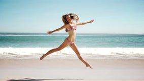 Giovane donna felice che salta sulla spiaggia nel cinemagraph video d archivio