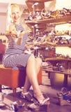 Giovane donna felice che sceglie due paia di nuove scarpe Fotografie Stock