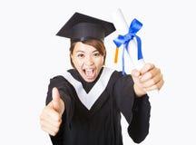 Giovane donna felice che si laurea mostrando pollice su Fotografie Stock Libere da Diritti