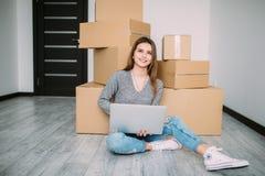 Giovane donna felice che si muove verso la nuova casa che si siede sul pavimento e sul computer portatile di uso vicino alle scat Immagine Stock Libera da Diritti