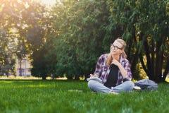 Giovane donna felice che si siede con il taccuino sull'erba Fotografia Stock