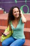 Giovane donna felice che si siede sui punti con un telefono cellulare Fotografia Stock Libera da Diritti