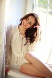 Giovane donna felice che si siede sul davanzale della finestra dentro la casa Fotografie Stock