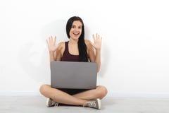 Giovane donna felice che si siede sul pavimento con le gambe attraversate e che per mezzo del computer portatile sul fondo bianco Fotografia Stock