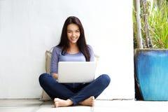 Giovane donna felice che si siede sul pavimento con un computer portatile Immagini Stock Libere da Diritti