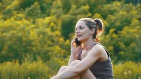 Giovane donna felice che si siede sul prato inglese verde e che parla sul telefono o sullo smartphone archivi video