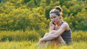 Giovane donna felice che si siede sul prato inglese verde e che parla sul telefono o sullo smartphone video d archivio