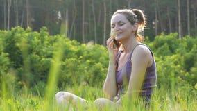 Giovane donna felice che si siede sul prato inglese verde e che parla sul telefono o sullo smartphone stock footage