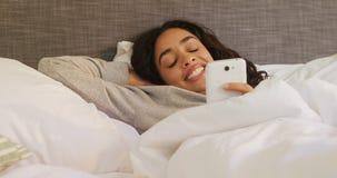 Giovane donna felice che si trova sul letto facendo uso del suo telefono cellulare 4K 4k video d archivio