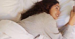 Giovane donna felice che si trova sul letto facendo uso del suo telefono cellulare 4K 4k stock footage