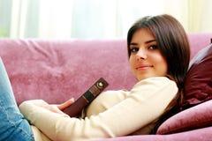 Giovane donna felice che si trova sul sofà con il libro Fotografia Stock Libera da Diritti