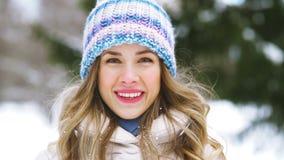 Giovane donna felice che soffia per nevicare nella foresta di inverno stock footage