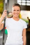 Giovane donna felice che sorride al centro della palestra di forma fisica Fotografie Stock Libere da Diritti
