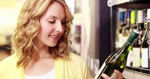 Giovane donna felice che sorride alla macchina fotografica con vino in sue mani archivi video