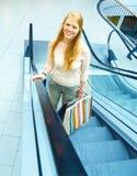 Giovane donna felice che sorride felicemente sulla scala mobile Fotografia Stock