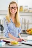 Giovane donna felice che studia nella cucina Immagine Stock