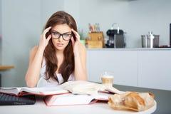 Giovane donna felice che studia nella cucina Fotografie Stock Libere da Diritti