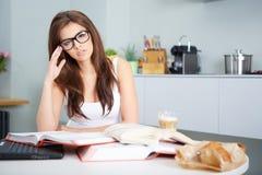 Giovane donna felice che studia nella cucina Immagini Stock Libere da Diritti