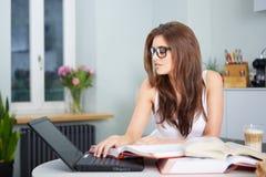 Giovane donna felice che studia nella cucina Fotografia Stock