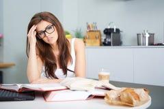 Giovane donna felice che studia nella cucina Fotografia Stock Libera da Diritti