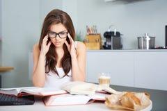 Giovane donna felice che studia nella cucina Immagini Stock