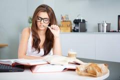 Giovane donna felice che studia nella cucina Fotografie Stock