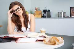 Giovane donna felice che studia nella cucina Immagine Stock Libera da Diritti