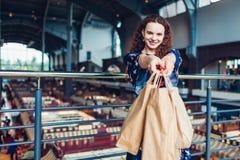 Giovane donna felice che tiene i sacchi di carta di acquisto nel centro commerciale immagine stock