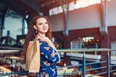 Giovane donna felice che tiene i sacchi di carta di acquisto nel centro commerciale immagine stock libera da diritti