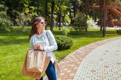 Giovane donna felice che tiene i sacchi di carta di acquisto nel parco di estate e che indossa attrezzatura d'avanguardia fotografia stock