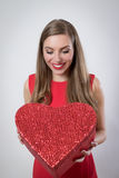 Giovane donna felice che tiene un grande San Valentino del presente del cuore Immagine Stock Libera da Diritti