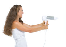 Giovane donna felice che usando hairdryer come pistola Fotografia Stock Libera da Diritti