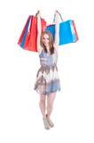 Giovane donna felice chegode della compera e dell'aumentare sui sacchetti della spesa Fotografie Stock Libere da Diritti