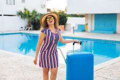 Giovane donna felice con bagagli blu che arrivano alla località di soggiorno Sta camminando accanto alla piscina Inizio di Fotografia Stock