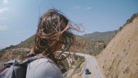 Giovane donna felice con capelli che soffiano nel vento che sorride alla macchina fotografica al punto soleggiato di vista al pon video d archivio