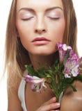 Giovane donna felice con i fiori rosa fotografia stock