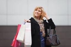 Giovane donna felice con i sacchetti della spesa fotografia stock