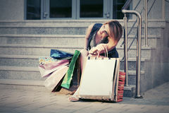 Giovane donna felice con i sacchetti della spesa che si siedono sui punti Fotografia Stock