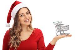Giovane donna felice con il cappello di Natale che tiene piccolo acquisto vuoto fotografia stock libera da diritti