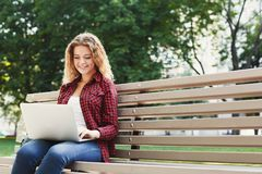 Giovane donna felice con il computer portatile all'aperto Immagine Stock