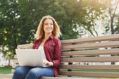 Giovane donna felice con il computer portatile all'aperto Fotografia Stock