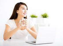 Giovane donna felice con il computer portatile in salone Fotografia Stock Libera da Diritti