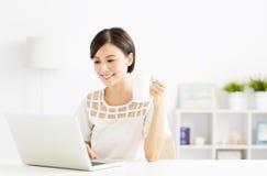 Giovane donna felice con il computer portatile in salone Immagini Stock Libere da Diritti