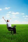 Giovane donna felice con il computer portatile sul prato Fotografie Stock