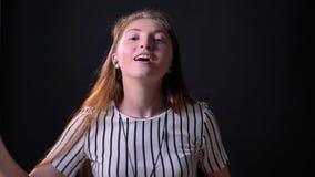 Giovane donna felice con il dancing lungo dei capelli dello zenzero e la musica d'ascolto tramite le cuffie, isolate su fondo ner archivi video
