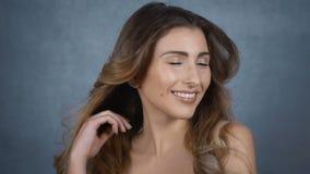 Giovane donna felice con il fronte perfetto isolato su fondo grigio video d archivio
