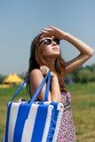 Giovane donna felice con il sacchetto della spiaggia Immagini Stock Libere da Diritti