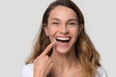 Giovane donna felice con il sorriso perfetto che esamina macchina fotografica immagini stock libere da diritti