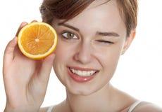 Giovane donna felice con l'arancio fotografia stock libera da diritti
